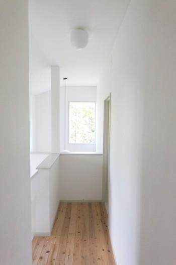 廊下もすべて白で統一。窓から雑木林の緑がこぼれる。