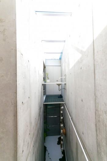 洗面台が宙に浮いている!? 白い扉の向こうが2階のトイレ。その下のグレーの扉が玄関ドア。