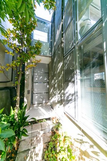 階段を上り、光が揺れる木陰の小道を行くと玄関ドアが現れる。ワクワクドキドキがあるアプローチが楽しい。