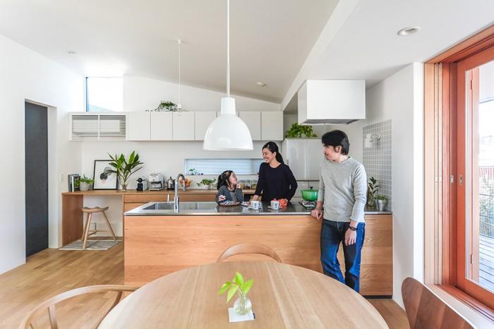 2階の西側にあるダイニングとキッチン。この家では、意図的に天井の高さに変化をつけている。「普通の感覚ですと天井は高ければ高いほどいいと思う方が多いですが、逆に天井高を下げることによって落ち着き感が出ることもあるんですね」。