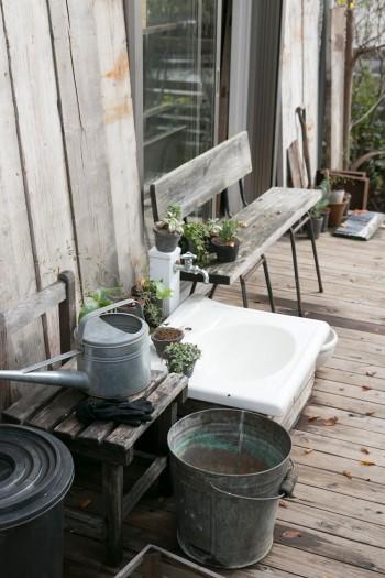 デッキの上の水場と休憩用のベンチ。ブリキのジョウロなどが経年の味わい。