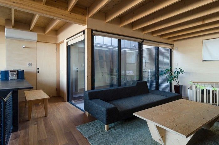 プライバシーを考慮して東西の両サイドには開口を設けず、その分、2階に中庭スペースをつくり光を採り入れている。右のテーブルはこの家のためのオリジナルデザイン。傾いた壁に合わせて、脚の部分を斜めにカットしている。