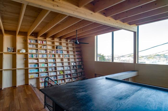 2階からパントリー越しに本棚と大きな開口を見る。大人数が訪れた時には、ダイニング、階段、リビングとそれぞれに居場所をみつけてくつろぐという佐藤邸。パントリーの上に乗ってお酒を飲む人もいるという。