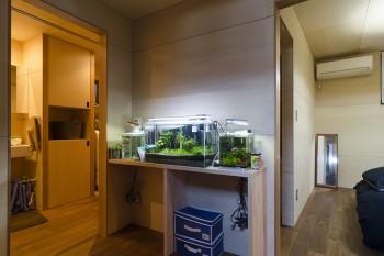 1階の右が寝室で左に水回り。中央には、帰宅時に明るいところがあった方がいいだろうと藤井さんの考えで水槽を置いた。