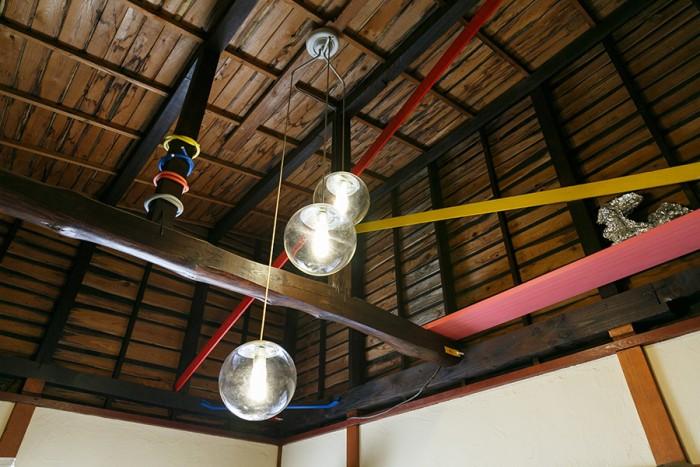 2階の一部屋は天井を外し、小屋裏を現しに。ところどころペイントした木部がアクセントになっている。球のかたちの照明器具は、電気屋さんにもらったもの。