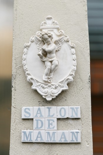 玄関脇の壁にアルファベットのタイルと天使のレリーフを貼って、薬膳料理教室の看板代わりに。