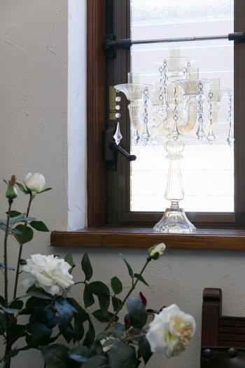 窓際には、造花のバラとガラス製のランプをしつらえて。
