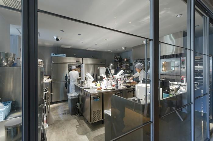 大きなガラス扉からキッチンの作業風景を見ることができる。