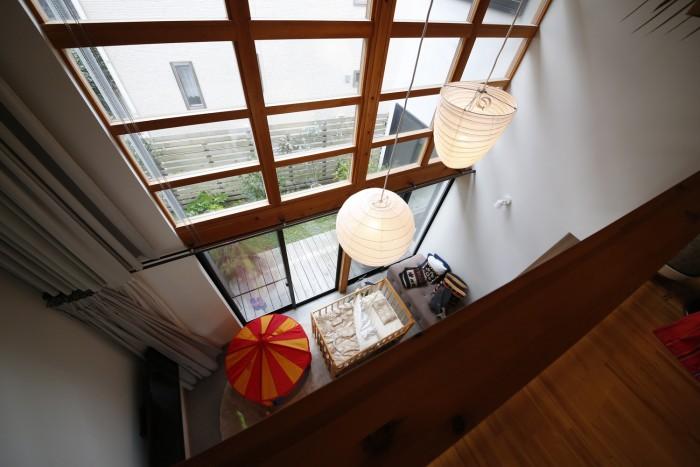 2階から吹き抜けを通して1階を見下ろす。千笑ちゃんのベビーベッドが見える。