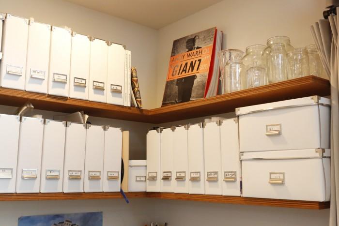 ワークデスクの上の棚に並んだファイルケースは、白で統一している。
