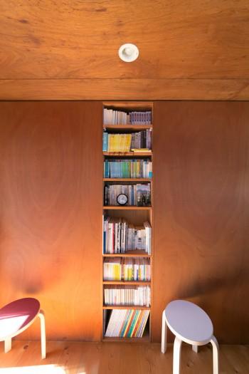 寝室の本棚。シンプルなアアルトのスツールが似合う。両サイドは向こう側の部屋の収納に。