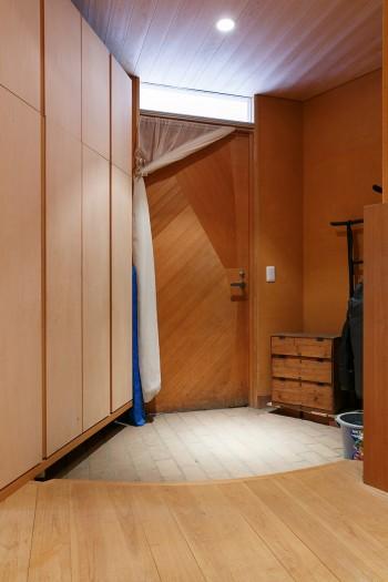 広々とした玄関ホール。玄関ドアも岩橋さんのデザイン。左手に大容量の収納が設けられている。