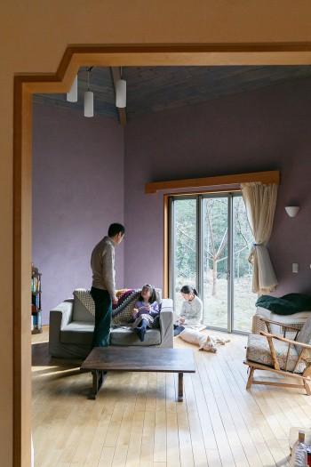 ラベンダー色の漆喰壁のリビングでくつろぐ。テーブルはSさんが古道具屋さんで求めたもの。「この家には古い家具や雑貨が不思議としっくりきます」。