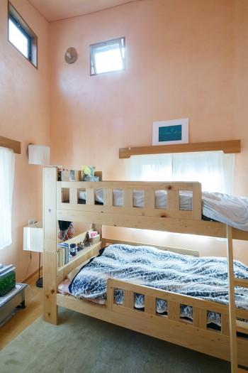 子ども部屋も壁はサーモンピンクに。天井が高いので、開口部を設けて空気が流れるようにしている。