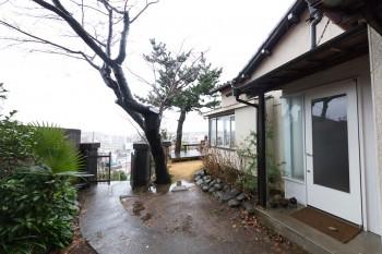 坂道や階段をどんどん登ってきた丘の上が柏邸。門柱の横には八重桜。