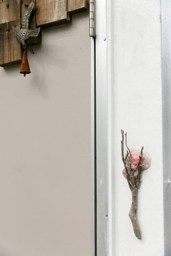 玄関扉脇の貝と流木でつくったオブジェは朋子さんの作品。