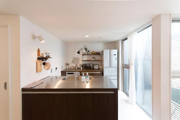 """ふたりで作業ができるよう、""""ぶつからない広さ""""を確保したキッチン。レンジフードは設置せず、昔ながらの換気扇で対応。"""