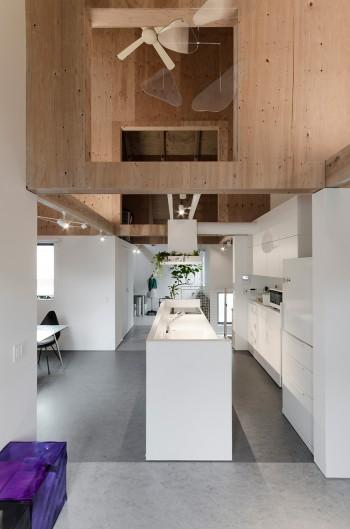 リビングからキッチンを通して奥にプレイルームを見る。床の色はクールなイメージを狙って、グレイを選んだ。