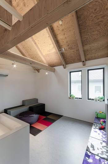 手前のキッチン、ダイニングとずれて配置されているため、個室的な落ち着きを感じさせるリビング。
