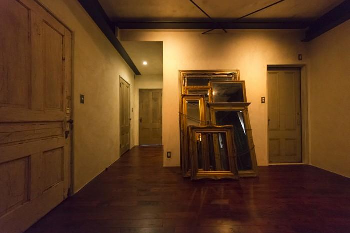 玄関を入って次の扉を開けると、アンティークの鏡を重ねて鎖で束ねたオブジェだけがある広い不思議な空間に出迎えられる。