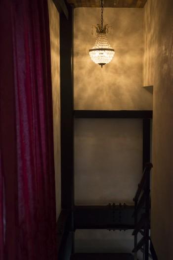 劇場用のカーテンのドレープ、シャンデリアが作る光の陰影、無骨なスチールの階段……、階段の踊り場もドラマチックな演出。