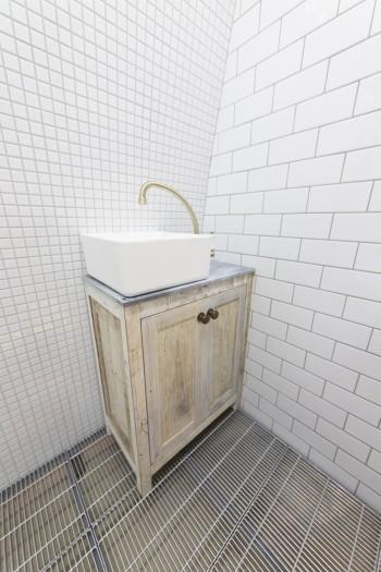 抑えた照明が多い中、1階のトイレだけは敢えて真っ白な蛍光灯を使い、床はグレーチング。「違和感を与えたかったんです」