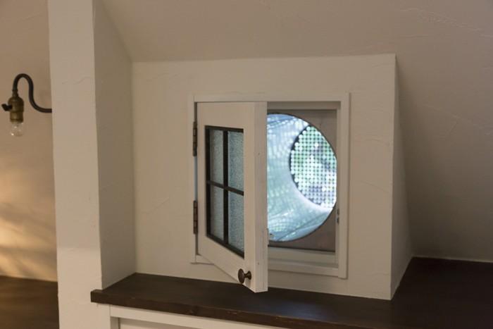 窓。カチャリと開けると筒があり、筒の先にメッシュが貼ってある。丸い屋根に窓を作るための工夫だ。