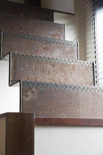 寝室からメゾネットに上る階段も鍛冶職人によるもの。錆の表情が美しい。踏み板は縞鋼板。