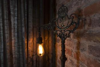 フィラメントが美しいエジソン球と、アンティークの台座を組み合わせたライトスタンド。ブリックタイルが柔らかい光を受ける。