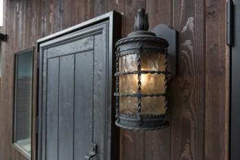 何度も作りなおしたというこだわりの玄関扉の横には、ディズニーランドでも使われている照明器具を玄関灯に。