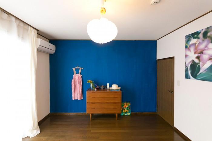 壁の一面のみブルーに塗られた寝室。計算されたディスプレイが美しく、1枚の絵のよう。