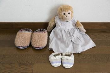 """娘さんの""""赤ちゃん""""(おさるさん)。もともと娘さんが着ていたドレスとはいていたベビーシューズ。左側は娘さんのスリッパ。"""