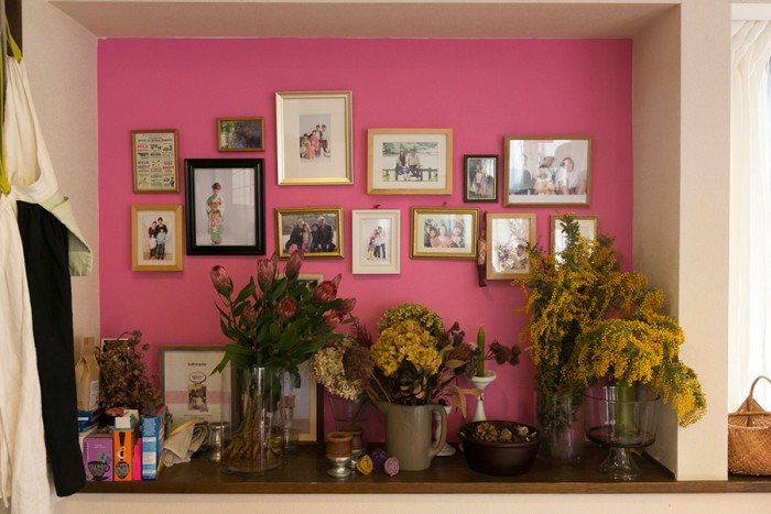 リビングを華やかに彩るピンクの壁。アースカラーの花とも好相性。家族の思い出の写真が絶妙なバランスで飾られている。