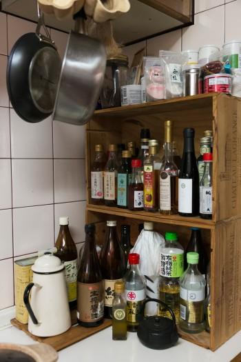 ワインの木箱を再利用したラックには、身体にやさしい調味料がズラリ。よく使う調理器具は見せる収納に。