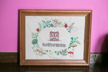 """屋号の「tottorante」は""""totto""""と""""リストランテ""""を合体させたもの。知人が刺しゅうしたというロゴは繊細でユニーク。ロゴのまわりをきのこやいちじく、れんこんなど全て食べ物が囲むという凝りよう。"""