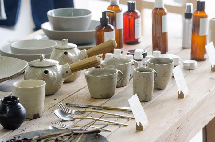 写真中央に並ぶのは福岡県久留米市で作陶を行う馬場勝文さんの作品。チークのハンドルが印象的な刷毛目急須。握りやすいハンドルは丈夫、熱湯を注いでも熱くなりにくい。手前に並べられているのは岐阜県の彫刻家、小西光裕さんの真鍮とステンレスを組み合わせたカトラリー。