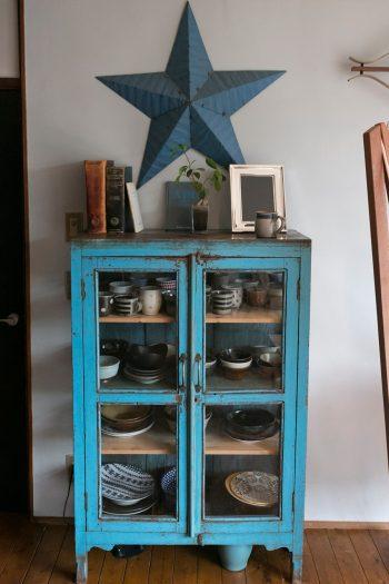 古道具屋で買ったブルーの戸棚回りは、青をテーマにコーディネイト。革表紙の古書がいい味を出してます。