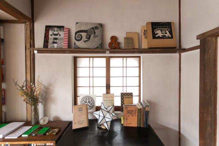 漆喰の壁や障子に、古い本のカバーが映える。鴨居を利用して本を飾る棚を作った。