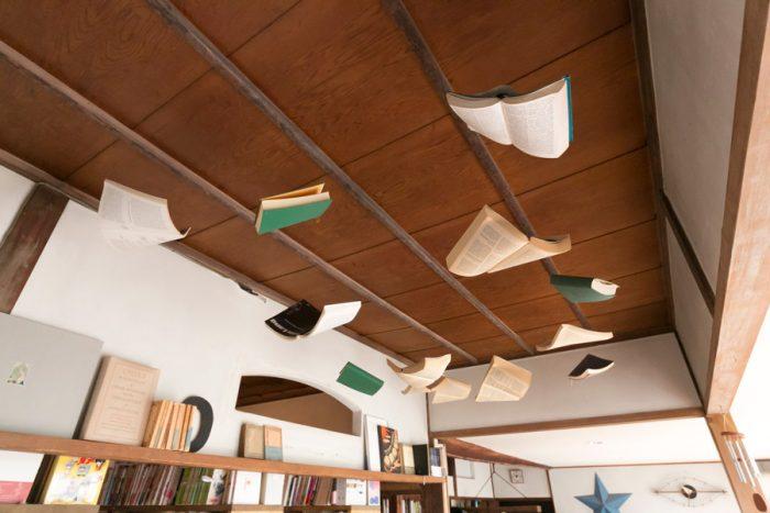 釣り糸で本を天井から吊っている。糸の端はビーズで留めて。板目の天井をバックに、本がフワフワと浮いている感じがおもしろい。