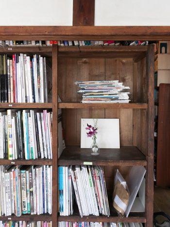 写真集や雑誌がちょうど収まるサイズの本棚。本をバックに、一輪挿しの花がよく似合う。