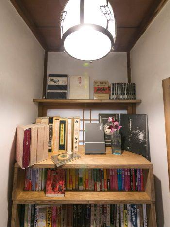 ここにも古書と花。この小さな本棚の前でカラダを丸めて本を読み耽りたくなる。
