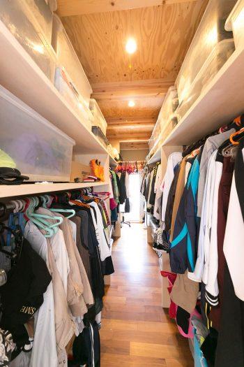 """ハンガーを使った""""掛ける収納""""でたたむ手間を省いた。季節により上段のケース内の衣服と入れ替えるだけ。"""