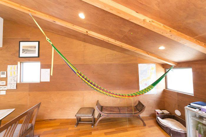 勾配天井と相性のよいハンモック。鮮やかな色が部屋のアクセントに。「形が気に入った」というベンチはバリ島から直輸入。