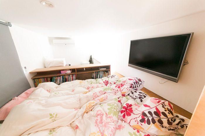 ロフトをベッドとして利用した夫婦の寝室。低い天井が安心感をもたらせ、深い眠りを誘う。奥の棚は、よく読む雑誌のサイズに合わせた設計になっている。