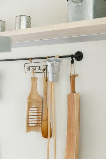 よく使う道具は、壁に掛けて使いやすく。カッティングボードは、飛騨高山の家具作家・阿部貢三さんの作品。家具の端材から生まれたもの。