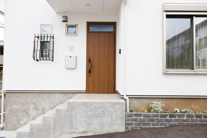 閑静な住宅街に立つ真っ白な一軒家。近隣の庭の緑も美しい。