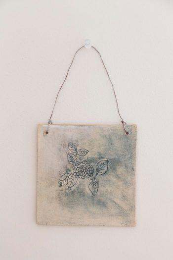 友人の川原真由美さんが絵を描き、陶芸家のくまがいのぞみさんが焼いた作品。後ろに美詠子さんの言葉「アマオト」入り。