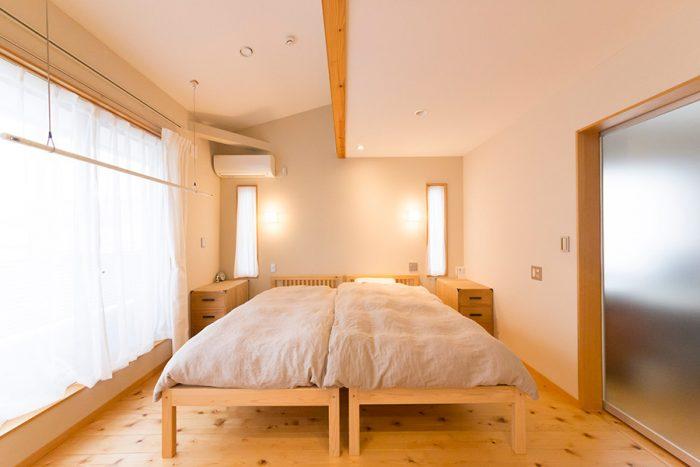シンメトリーにデザインしたベッドルーム。両ベッドサイドのキリの棚は、アイアンの取手に付け替えたそう。