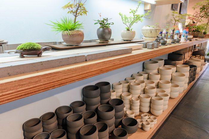 丸みを帯びた品品オリジナルの鉢は信楽で作られている。優しい生成色のマットホワイトと和の空間にもしっくりなじむシックなブラックの2色。すべて若手作家によって作られており、鉢の制作を通じて支援につながっている。