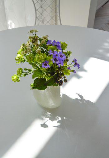 ダイニングテーブルに置かれた花の緑と紫の色味が白い室内に映える。